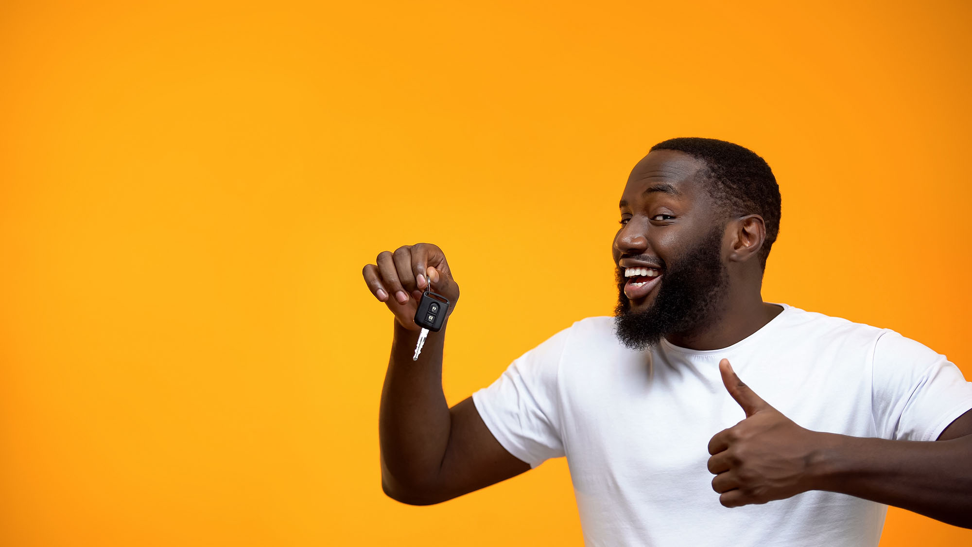 Excited Afro-American man holding car key and showing thumbs up, purchase